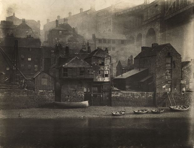 Type : Photograph Medium : Print-black-and-white Description : This black-and-white photograph shows the buildings along Gatehead's riverside by the High Level Bridge. The River Tyne in the foreground is at low tide with boats on the shore.Description and Views Collection : Local Studies Printed Copy : If you would like a printed copy of this image please contact Newcastle Libraries www.newcastle.gov.uk/tlt quoting Accession Number : 001159